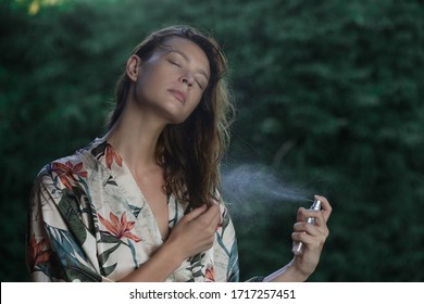 Woman refreshing with thermal water against summer heatwave. Woman spraying body or hair mist, summertime skincare and haircare concept.