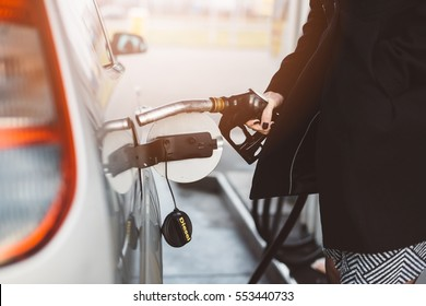 Woman refueling car with diesel at the gas station
