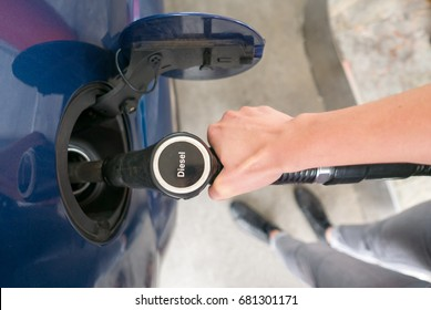 Woman refueling the car with diesel oil at petrol station