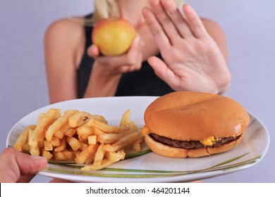 Woman refuses to eat junk food and choose fruits. Healthy eating and active lifestyle concept
