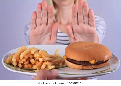 Woman refuses to eat junk food . Healthy eating and active lifestyle concept
