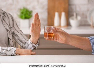 Woman refusing to drink whiskey at home. Concept of alcoholism