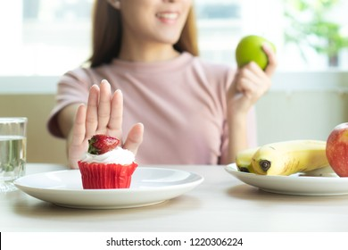 woman refusing to eat sweet bakery or cake during diet session for slim shape and good health.