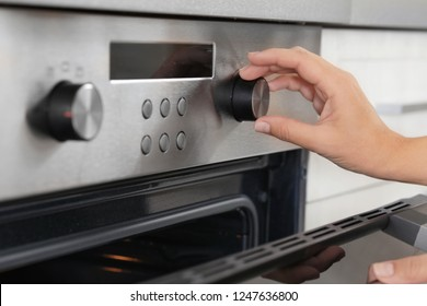 Woman regulating cooking mode on oven panel, closeup