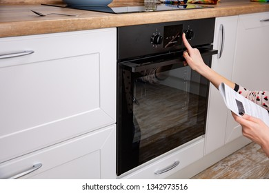Woman regulating cooking mode on oven panel
