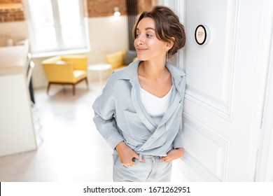 Woman regulating heating temperature with a modern wireless thermostat installed on the white wall at home. Smart home heating regulation concept