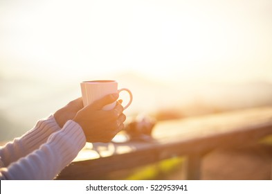 Woman  relax and drinking  coffee and  tea sun sitting outdoor in sunshine light enjoying her morning coffee. In the house nature soft.