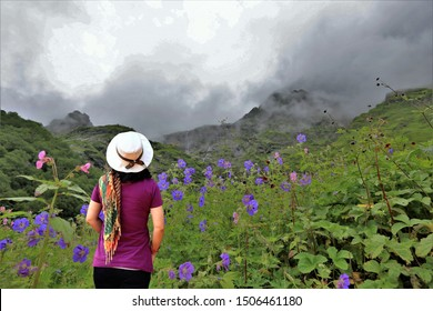woman relax and hppy hours on hill,fog on mountain in India,beautiful blue flower(blue popy) with fog on Valley of flowers national park,India