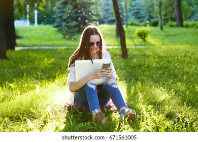 Woman relax with a mobile in a Break time outdoor. Young woman using cellphone and sitting on the grass on park at sunny day