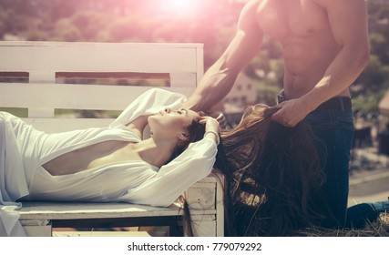 Woman relax on bench on sunny summer day. Girl with long hair and male torso with muscle. Beauty, look concept. Romance, relationship, family. Vacation, travel, wanderlust.