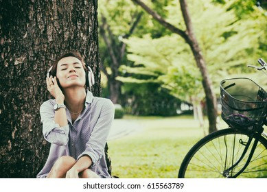 Woman  relax and reading a book while listening music with headphone in the nature green park, girl happy, vintage tone.  Lifestyle Concept