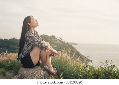 A woman relax sea view on the top of a rock . A woman on the top of a rock enjoys the view of sunset over an autumn forest