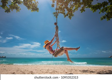 woman relax sitting and playing around on wooden swing under plam tree at sunny on the island, summer time vacation and weekend relax funny happy time