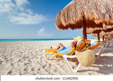 Woman at relaxation under parasol at Caribbean Sea