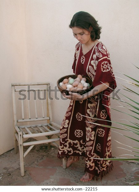 A woman in relaxed indigenous textile dress walks with a bowl of colorful eggs in a calming rustic environment.