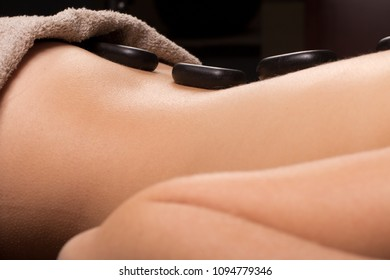 Woman relaxed lying with spa stones at her back