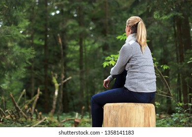 A Woman relaxed on a tree trunk in a forest