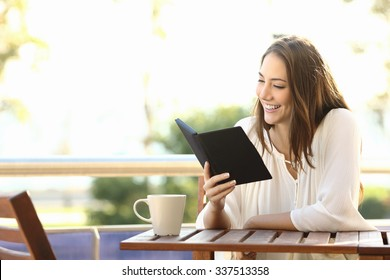 Woman relaxed reading a book in an ebook reader in a bar or at home