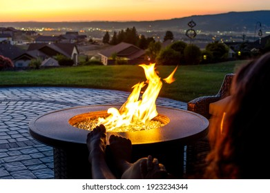 A woman relaxes by a roaring firepit on a paver patio at sunset overlooking the Spokane Valley, in Washington State, USA