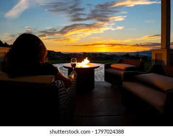 A woman relaxes with a glass of wine at night in front of an outdoor firepit on a patio of a luxury home overlooking a city and valley