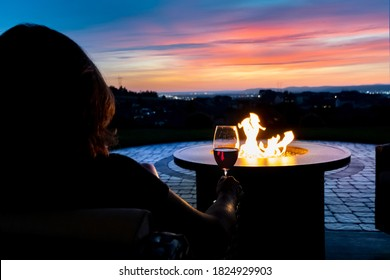 A woman relaxes with a glass of wine at sunset by a fire pit on the patio of a luxury home overlooking the Spokane valley and city in Spokane, Wa USA