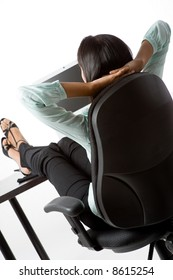 A woman relaxes with her feet on the desk at work