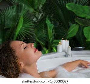 A woman relaxes in hot bath tub with soap foam. Luxury spa interior of bathroom with tropical plants leaves.