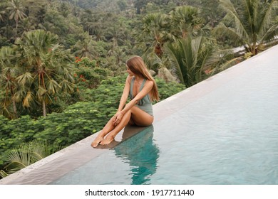 Woman relaxes in a luxury infinity pool overlooking the jungle in Ubud, Bali. A girl sits on the edge of the infinity pool against the backdrop of jungle nature