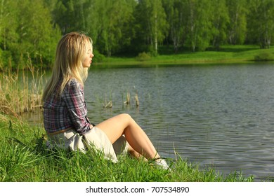 Woman relaxes on lake shore sitting on the green grass. Summer holidays concept.