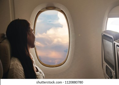 A woman relaxes on the plane while flying, to go on vacation, on her comfortable seat and from the window you can see the clouds of the sky. Concept of: travel, vacation and transport.