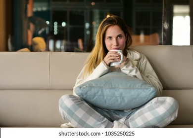 A woman relaxes on the sofa at home, hugging a pillow and watching a movie in canvas and smile. Concept of: leisure, relax, tv.