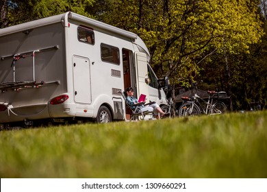 Woman relaxes and reads a book near the camping . Caravan car Vacation. Family vacation travel, holiday trip in motorhome RV.