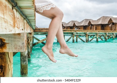 Woman relaxes sitting on the edge of a wooden jetty, legs swing near the water surface in the background Maldives water bungalows