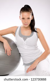 Woman relaxing after exercises with fitness ball on white background