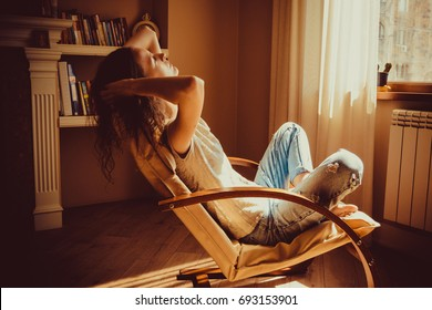Woman relaxing after work in comfortable modern chair near window in livingroom. Warm natural light. Cozy home. Casual clothing. Casual style indoor. Room interior. Tired and thoughtful woman.