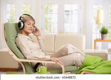 Woman relaxing in armchair at home enjoying music in headphones, smiling.?