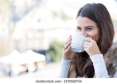 Woman relaxing at balcony enjoying sunrise. Good morning