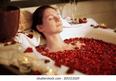Woman relaxing in bathtub with rose blossoms