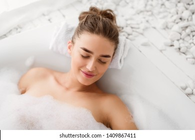 Woman Relaxing In Bathtube With Soap Foam, Lying With Closed Eyes
