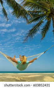 Woman relaxing at the beach on a hammock
