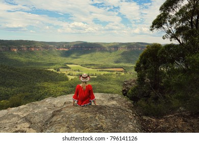 Woman relaxing with a beautiful vista of blue mountains cliffs and valley views