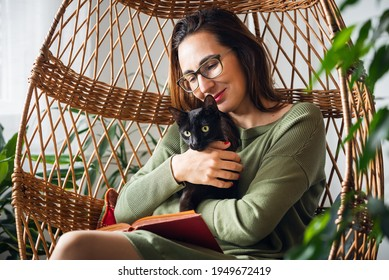 Woman relaxing with book at home with her balck kitten pet.  Woman reding book in swing chair at home on sunny day. Domestic lifestyle