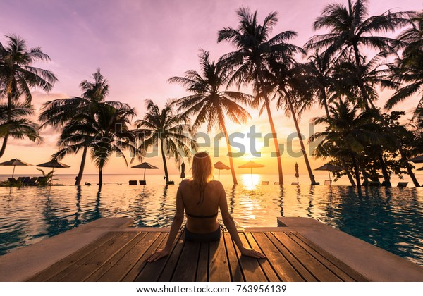 Woman relaxing by the pool in a luxurious beachfront hotel resort at sunset enjoying perfect beach holiday vacation
