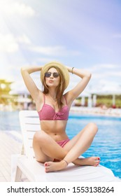 Woman relaxing in chaise lounge at the poolside