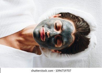 Woman relaxing with a charcoal facial mask