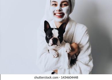 Frau entspannend mit einer Kohle Gesichtsmaske zu Hause mit ihrem Hund.Schöne Frau mit Ton oder Schlammmaske auf ihrem Gesicht auf weißem Hintergrund