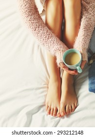 Woman relaxing at cozy home atmosphere on the bed. Young woman with beautiful skin and nails with cup of cocoa or coffee in her hands enjoying comfort. Soft light and comfy beauty natural lifestyle.