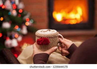 Woman relaxing with a cup of hot chocolate sitting in an armchair by the fireplace and christmas tree - closeup on winter evening relaxation detail