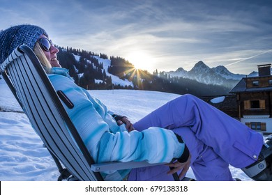 Woman relaxing in deck chair after skiing