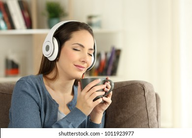Woman relaxing drinking and listening to music with eyes closed sitting on a couch in the living room at home